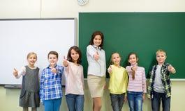 Gruppen av skolaungar och lärarevisning tummar upp royaltyfri foto