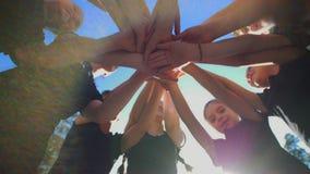 Gruppen av skolaungar utför motivational hälsning för sportar med händer på lekplats av gårdfotboll på den soliga dagen