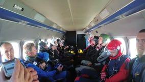 Gruppen av skydivers sitter inom en liten nivå som väntar på ett hopp arkivfilmer