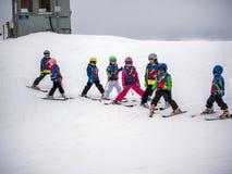 Gruppen av små skidåkare förbereder sig för nedstigningen av monteringen Österrike Zams på 22 Februari 2015 Arkivfoton