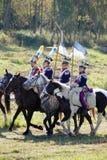Gruppen av soldater-reenactors rider hästar, två män bär flaggor Arkivfoton