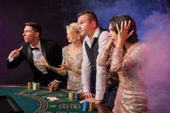 Gruppen av stilfulla rika vänner spelar poker på kasinot royaltyfri foto