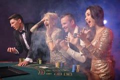 Gruppen av stilfulla rika vänner spelar poker på kasinot arkivfoton
