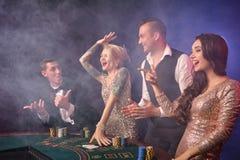 Gruppen av stilfulla rika vänner spelar poker på kasinot fotografering för bildbyråer