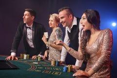 Gruppen av stilfulla rika vänner spelar poker på kasinot arkivfoto