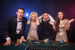 Gruppen av stilfulla rika vänner spelar poker på kasinot arkivbild