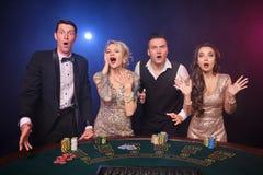 Gruppen av stilfulla rika vänner spelar poker på kasinot royaltyfria bilder