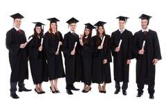 Gruppen av studenten avlägger examen med deras diplom Royaltyfri Bild