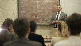 Gruppen av studenter i ett klassrum som lyssnar som deras lärare, rymmer en föreläsning stock video