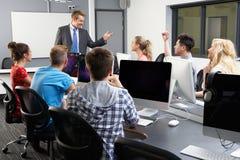 Gruppen av studenter med mannen handleder In Computer Class arkivbilder