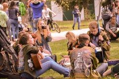 Gruppen av studenter sjunger sången som vilar på gräsmattan under berömmen av Victory Day på 9 kan 2017 i staden av Irkut royaltyfria bilder