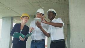 Gruppen av teknikerer och experter diskuterar om konstruktionsplats arkivfilmer