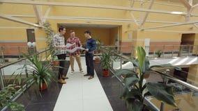 Gruppen av teknikerer står i shoppingkorridoren som dekoreras med blomkrukor lager videofilmer