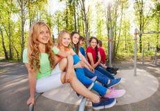 Gruppen av tonår sitter på brachiating på lekplatsen Royaltyfri Foto