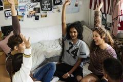 Gruppen av tonåringar i ett sovrum beväpnar lyftt royaltyfria bilder