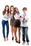 Gruppen av tonår som använder mobil, ringer Royaltyfri Foto
