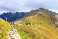 Gruppen av turister går till överkanten av Kasprowyen Wierch i Tatra berg Fotografering för Bildbyråer
