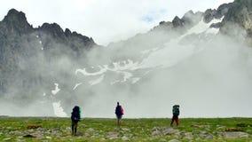Gruppen av turister med att fotvandra vandrar att komma i höga snöig berg med moln i den Kavkaz regionen arkivfilmer