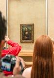 Gruppen av turister samlade runt om Mona Lisa i Louvremuseet Arkivfoto