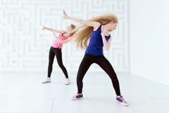 Gruppen av två unga kvinnor som gör en kondition, dansar genomkörare Arkivbilder