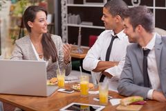 Gruppen av unga Businesspeople tycker om i lunch på restaurangen Royaltyfria Foton