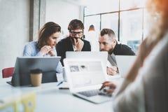 Gruppen av unga coworkers arbetar tillsammans den moderna kontorsstudion Lycklig konversation för affärslagdanande horisontal _ arkivbild