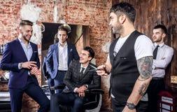 Gruppen av unga eleganta positiva män poserar i inre av frisersalongen arkivbild