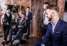 Gruppen av unga eleganta positiva män poserar i inre av frisersalongen royaltyfri fotografi