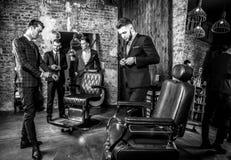 Gruppen av unga eleganta positiva män poserar i inre av frisersalongen Royaltyfri Bild