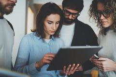 Gruppen av unga entreprenörer söker efter en affärslösning under arbetstid på det soliga kontoret arkivbild