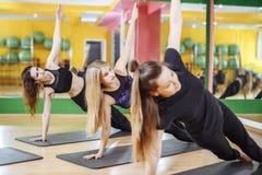 Gruppen av unga kvinnor som gör yoga, poserar i studiogrupp Kondition sport, utbildande livsstilbegrepp Royaltyfria Bilder