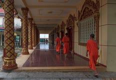 Gruppen av unga sydostliga asiatiska buddistiska munkar promenerar hallet i Wat Krom i Sihonoukville, Cambodja Arkivfoto