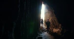 Gruppen av unga utforskare i hjälmar skriver in till den mörka grottan lager videofilmer