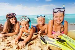 Gruppen av ungar lägger på stranden, i att snorkla maskeringar arkivbild