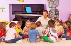 Gruppen av ungar sitter och lyssnar till läraren berättar berättelse Arkivbild