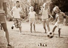 Gruppen av ungar som spelar fotboll tillsammans på grön gräsmatta parkerar in Fotografering för Bildbyråer