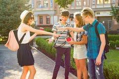 Gruppen av ungdom har gyckel, lyckliga tonåringvänner som går som talar tycka om dag i staden royaltyfri fotografi