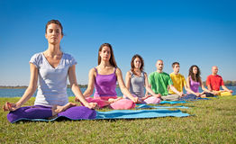 Gruppen av ungdomar har meditation på yoga att klassificera. Arkivfoto