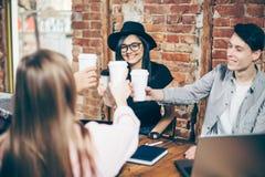 Gruppen av ungdomarfirar slutet av ett lyckat projekt i ett kafé arkivbild