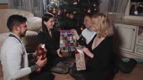 Gruppen av ungdomarger gåvor till varandra under trädet i julinre, beröm för nytt år stock video