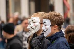 Gruppen av ungdomarsom kl?s alla i svart, g?r ut p? gatan att visa med anonyma maskeringar fotografering för bildbyråer
