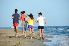 Gruppen av ungdomarsom kör i sanden på kusten av en strand förbi havet på solnedgången under en solig sommarferie, semestrar Arkivbilder