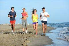 Gruppen av ungdomarsom kör i sanden på kusten av en strand förbi havet på solnedgången under en solig sommarferie, semestrar Arkivbild