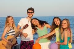 Gruppen av ungdomarsom tycker om stranden, festar med att spela gitarr a Fotografering för Bildbyråer