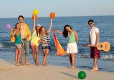 Gruppen av ungdomarsom tycker om stranden, festar med gitarren och ballo Arkivfoto