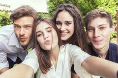 Gruppen av ungdomartar en selfie som tillsammans kramas royaltyfri bild
