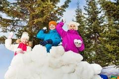 Gruppen av ungelek kastar snöboll leken tillsammans Arkivbilder