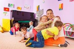 Gruppen av ungepojkar och flickor kramar läraren arkivbild