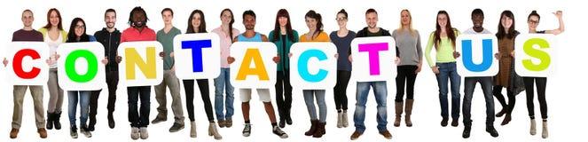 Gruppen av ungt mång- etniskt folk som rymmer ord, kontaktar oss arkivfoton