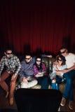 Gruppen av vännen i exponeringsglas 3d har hållande ögonen på tv för gyckel Fotografering för Bildbyråer